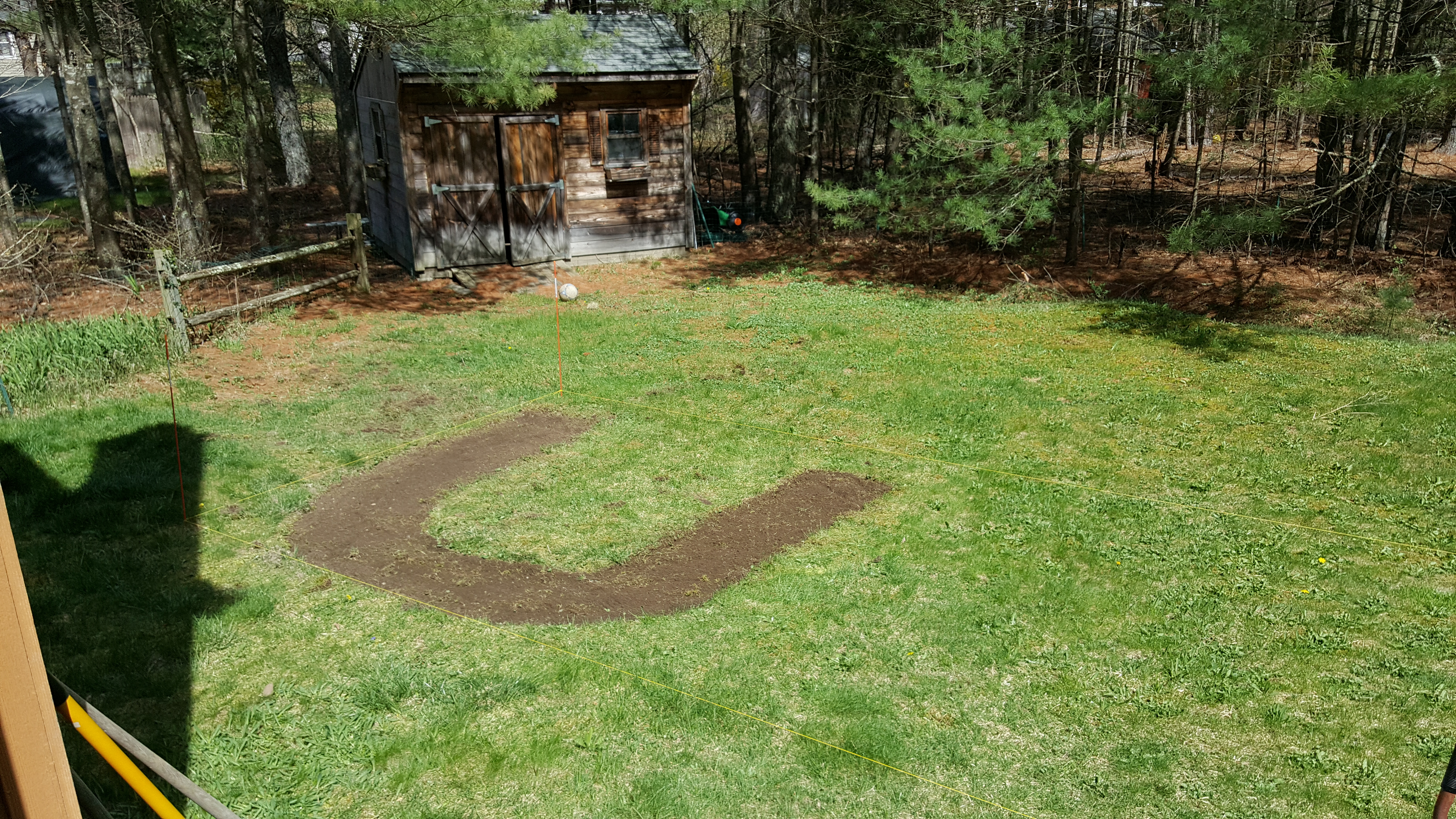 A letter 'U' cut into a green lawn. Looks about 6 feet each legs, the exposed earth is dark, slightly damp looking soil. There is a shed in the background.
